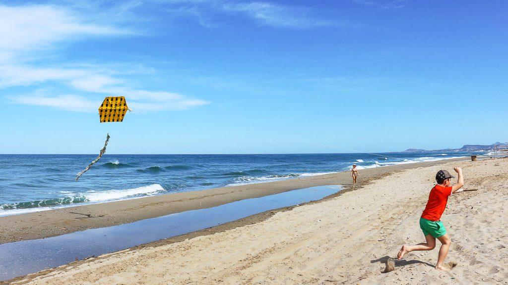 Aitvarai Kretos danguje. Berniukas paplūdimyje leidžia aitvarą. Kreta, Graikija | Mano Kreta